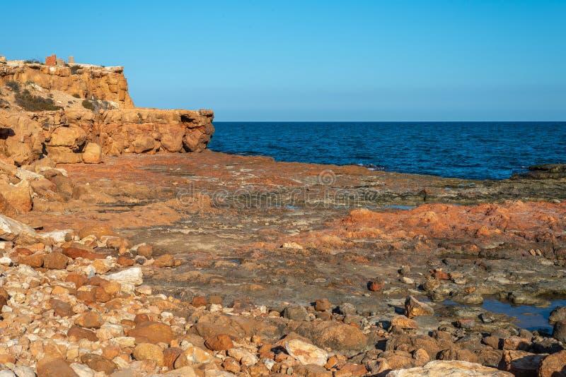 Взгляд теплых желтых песочных скал морем стоковое изображение