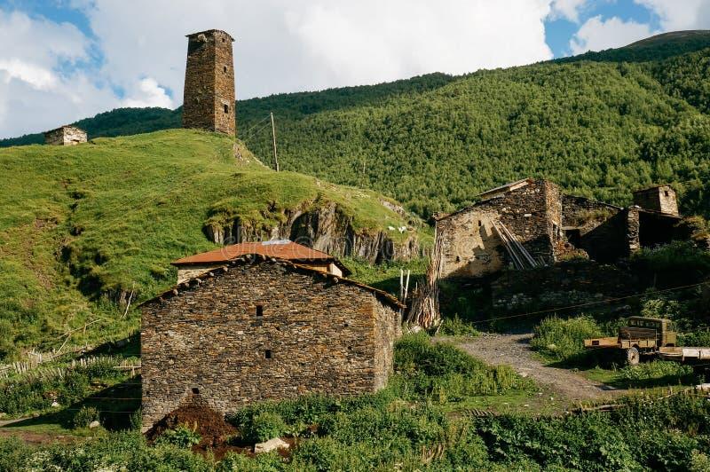 взгляд травянистого поля с старыми выдержанными сельскими зданиями и холмами на предпосылке, Ushguli, svaneti, стоковое фото rf