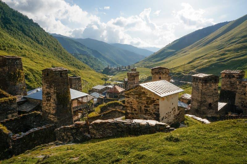 взгляд травянистого поля с старыми выдержанными сельскими зданиями и холмами на предпосылке, Ushguli, стоковая фотография