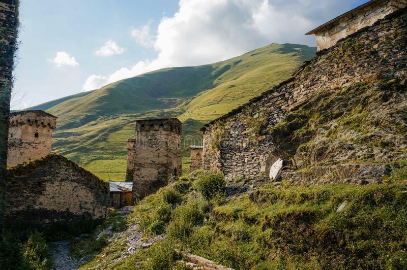 взгляд травянистого поля с старыми выдержанными сельскими зданиями и холмами на предпосылке, Ushguli, стоковое изображение