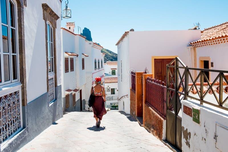 Взгляд улицы внутри небольшого испанского городка Tejeda в острове Гран-Канарии с туристской женщиной идя на летний день с взгляд стоковая фотография rf