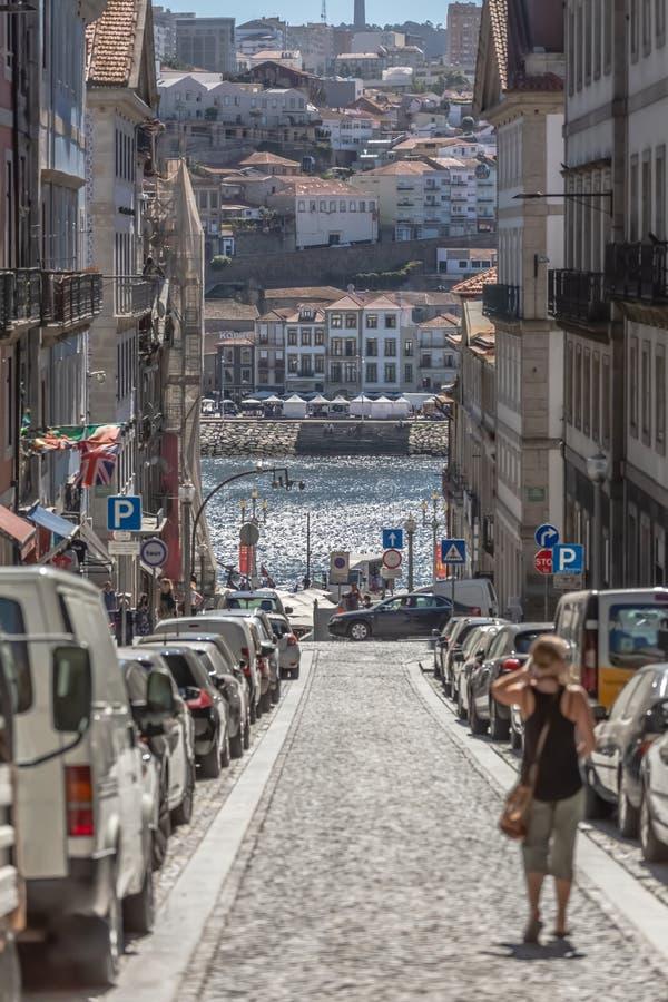 Взгляд улицы в центре города Порту, с традиционными зданиями, люди, корабли стоковая фотография