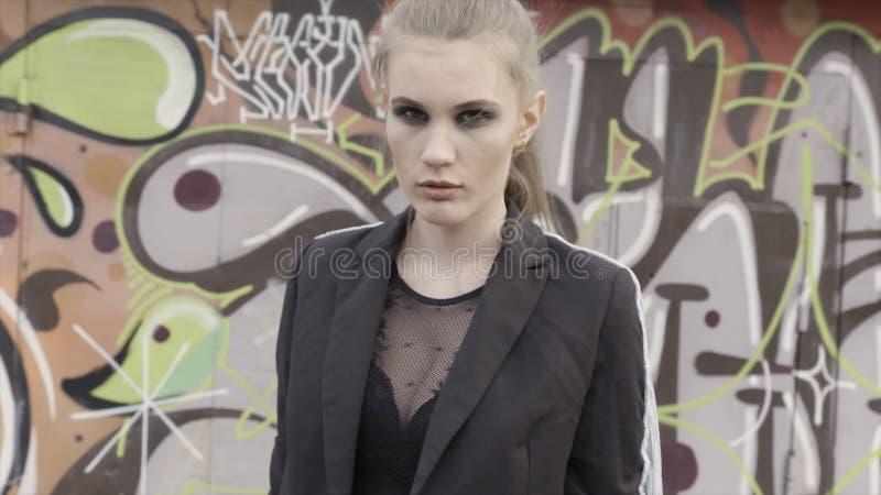 Взгляд улицы моды и сексуальной женщины с русыми волосами представляя около стены граффити E Девушка с темным макияжем стоковая фотография rf