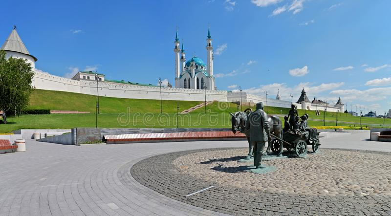 Взгляд утра квадрата названного после Asgat Galimzhanov на фоне солнечной панорамы Казани Кремля стоковая фотография