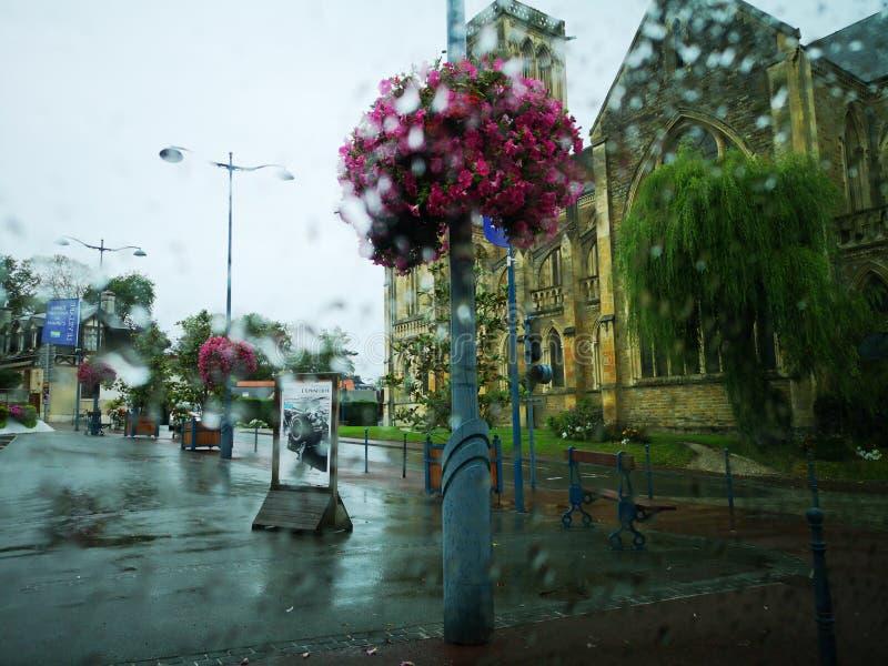 Взгляд цветков и церков на улице во время дождя изнутри автомобиля стоковое фото