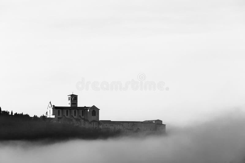 Взгляд церков StFrancis в Assisi в середине тумана под глубоким небом с облаками стоковое фото rf