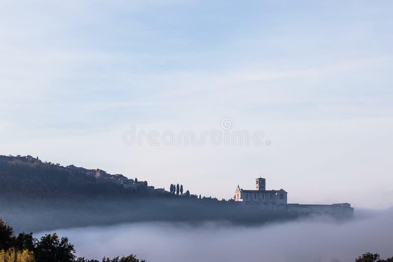 Взгляд церков StFrancis в Assisi в середине тумана под голубым небом с облаками стоковые фотографии rf