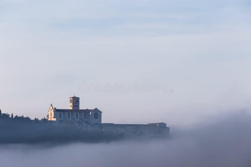 Взгляд церков StFrancis в Assisi в середине тумана под голубым небом с облаками стоковое фото
