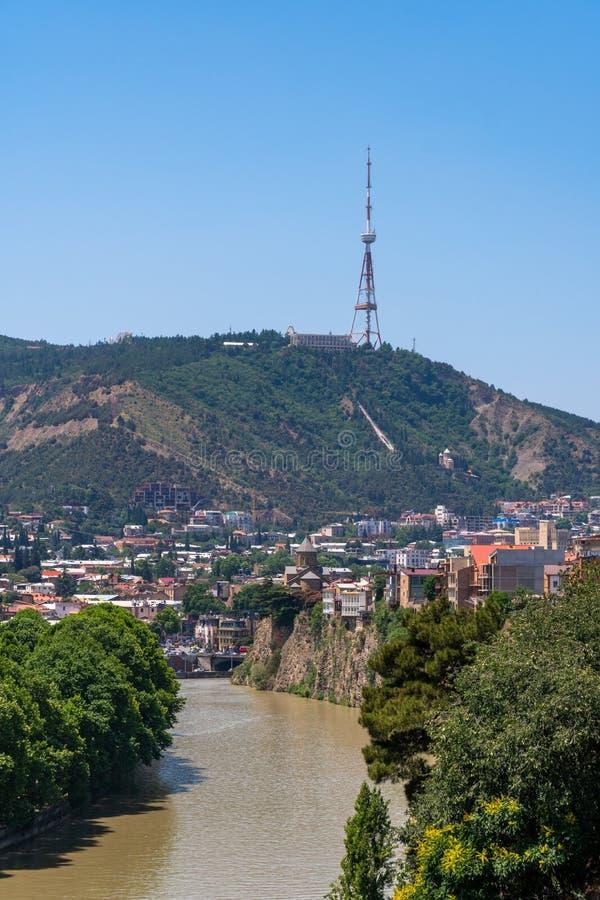 Взгляд через реку Mtkvari над старым районом городка к башне ТВ Тбилиси на горе Mtatsminda стоковые изображения rf