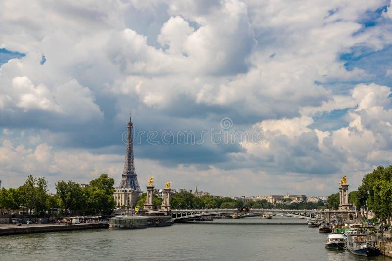 Взгляд Эйфелевой башни вдоль Рекы Сена Мост Александра треть в Париже Яркий и облачное небо стоковое изображение rf