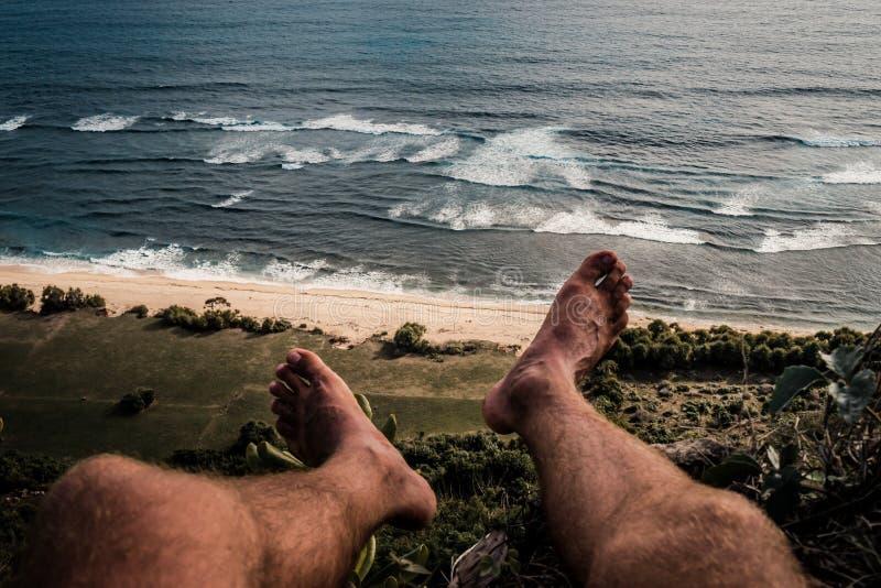 Взгляд POV ног на холме и океане стоковые изображения