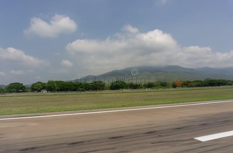 Взгляд Skyscape от ясного стеклянного места у окна воздушных судн к земле и горы под белыми пушистыми облаками и голубым небом по стоковое фото