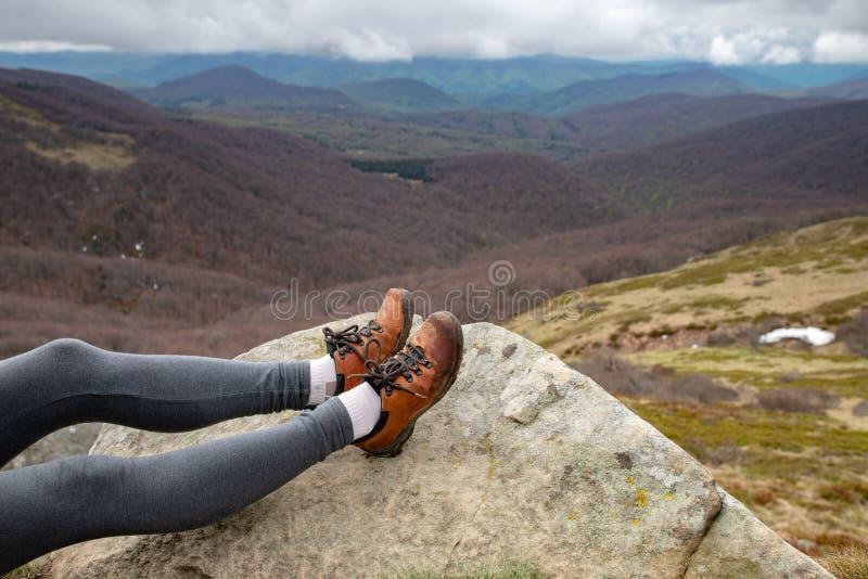 Взгляд women& x27; ноги s в trekking ботинках Отдыхая турист в горах стоковое изображение rf