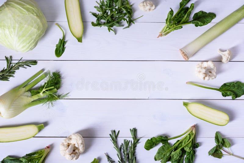 Взгляд высокого угла свежих зеленых veggies Цветная капуста, фенхель, шпинат и лук-порей над белой предпосылкой стоковое изображение