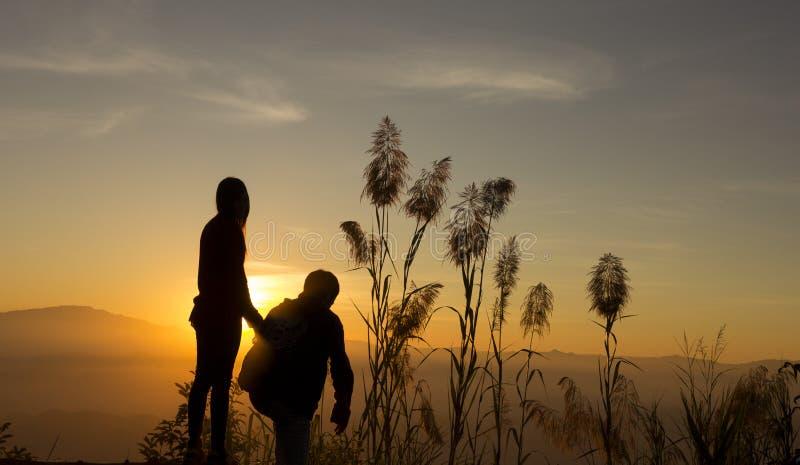 Взгляд детенышей силуэта 2 захода солнца к заходу солнца стоковая фотография rf