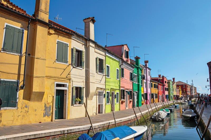 Взгляд красочных зданий, людей и шлюпок перед каналом на Burano стоковые фотографии rf