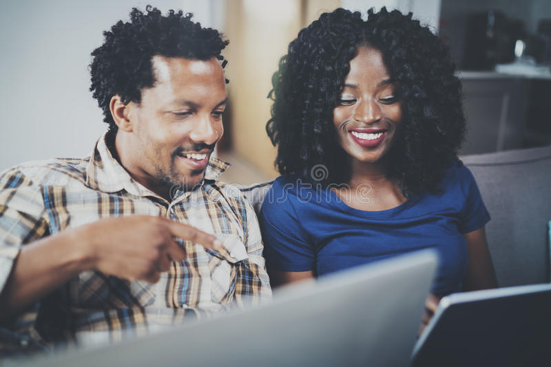 Взгляд крупного плана африканских пар имея остатки на доме: черная девушка сидя на софе, держащ таблетку касания и смеяться над стоковое изображение rf