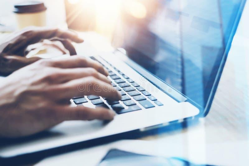 Взгляд крупного плана бизнесмена работая на солнечном офисе на современной компьтер-книжке Мужские руки печатая на клавиатуре тет