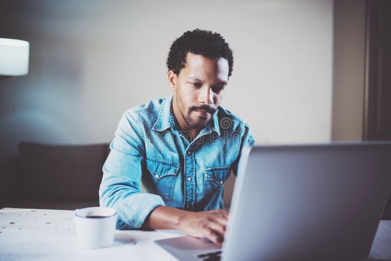 Взгляд крупного плана задумчивого бородатого африканского человека используя компьтер-книжку на coworking студии на деревянном ст стоковое изображение