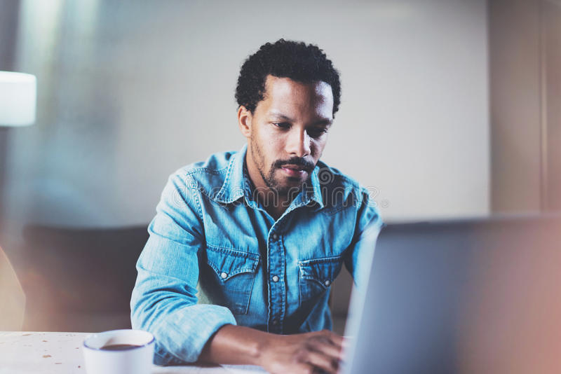 Взгляд крупного плана задумчивого бородатого африканского человека используя компьтер-книжку на coworking космосе на деревянном с стоковое изображение rf