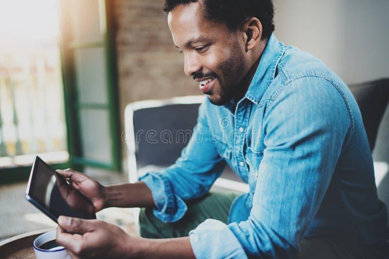 Взгляд крупного плана молодого бородатого африканского человека используя таблетку пока сидящ на софе дома Люди концепции работая стоковые фотографии rf