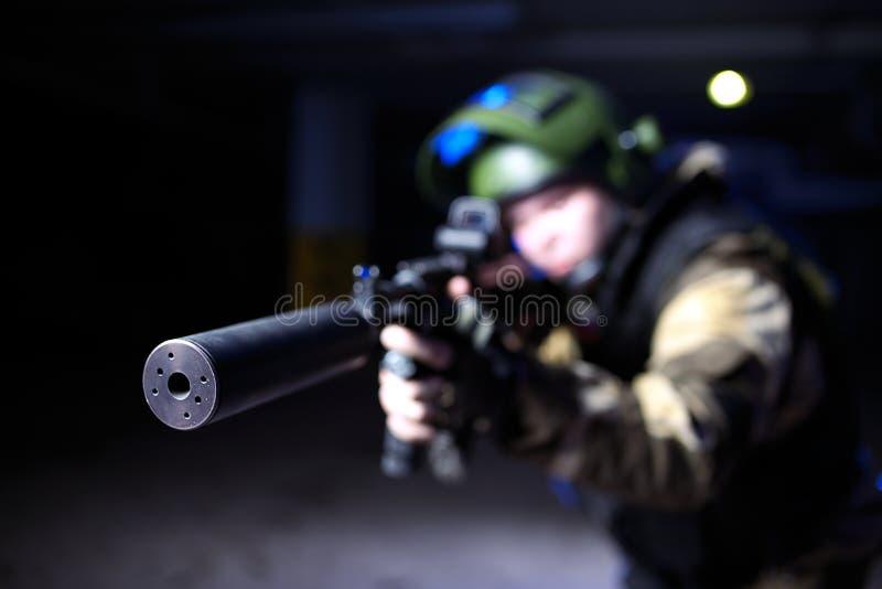 Взгляд крупного плана на звукоглушителе на оружие mashine в воинских руках стоковая фотография