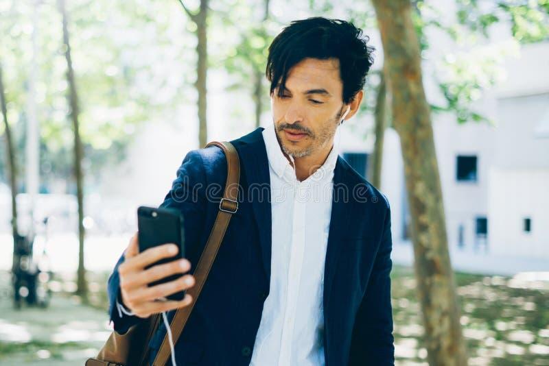 Взгляд крупного плана привлекательного молодого бизнесмена используя smartphone для listining музыки пока идущ в парк города гори стоковое фото rf