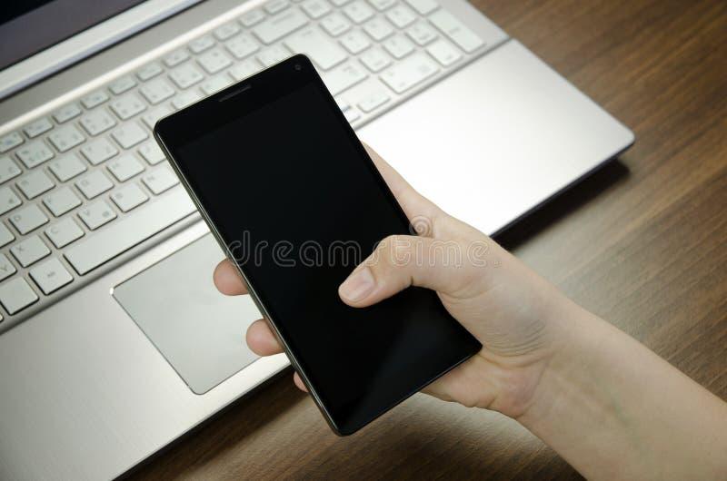 Взгляд крупного плана руки ` s женщины при пальцы держа черный smartphone на серебряной клавиатуре компьтер-книжки лежа на деревя стоковые фотографии rf