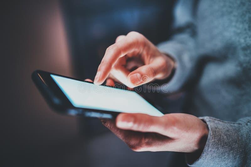 Взгляд крупного плана smartphone держа в руках Экран женских пальцев касающий белый пустой Горизонтальная, запачканная предпосылк стоковое фото