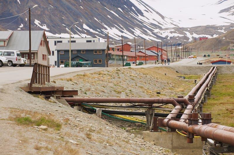 Взгляд к улице Longyearbyen с кипятильными трубами на переднем плане в Longyearbyen, Норвегии стоковое изображение