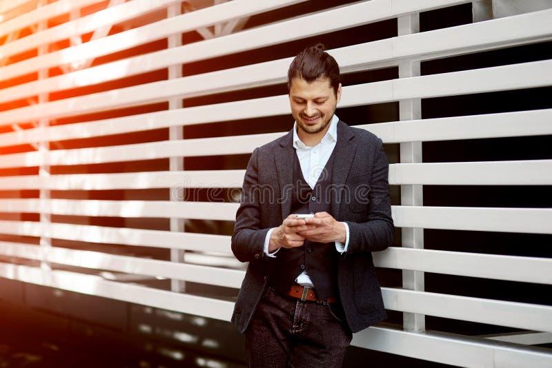 Взгляд молодого привлекательного бизнесмена используя smartphone outdoors стоковая фотография