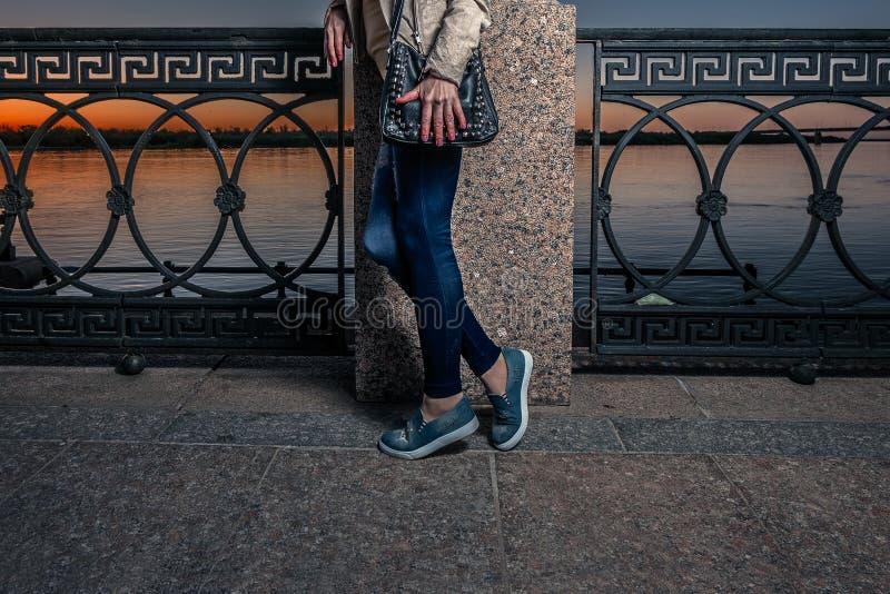 Взгляд моды улицы с джинсами, теннисной обувью и черной кожаной сумкой Маленькая девочка представляя на обваловке реки в фронте стоковое изображение