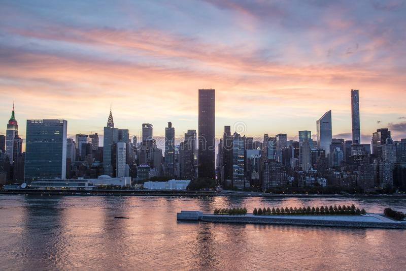 Взгляд на Манхаттане от города во время захода солнца, Нью-Йорка Лонг-Айленд, США стоковые изображения