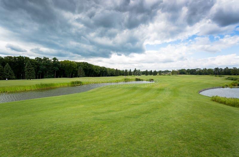 Взгляд на поле для гольфа на холодном дне с ненастными облаками стоковое изображение rf