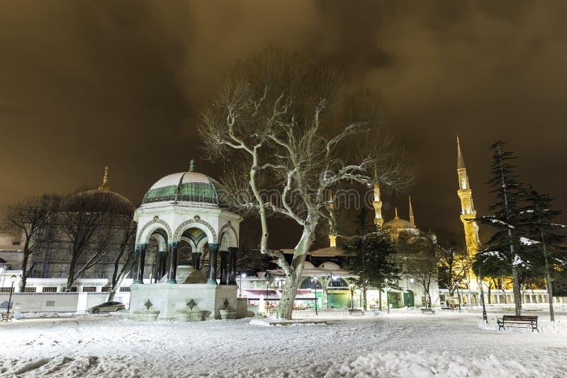 Взгляд ночи зимы Snowy мечети Sultanahmet и немецкого фонтана в Стамбуле стоковая фотография rf