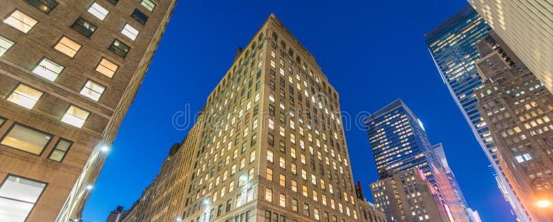 Взгляд ночи зданий Нью-Йорка от уровня улицы стоковые изображения