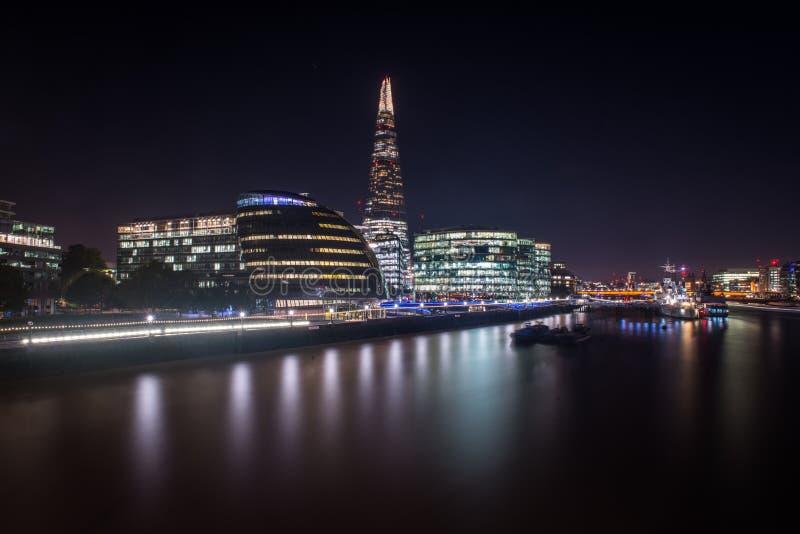 Взгляд ночи моста Лондона и современных зданий на южном банке стоковое изображение