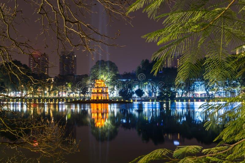 Взгляд ночи озера Hoan Kiem и черепаха возвышаются в Ханое стоковые фотографии rf