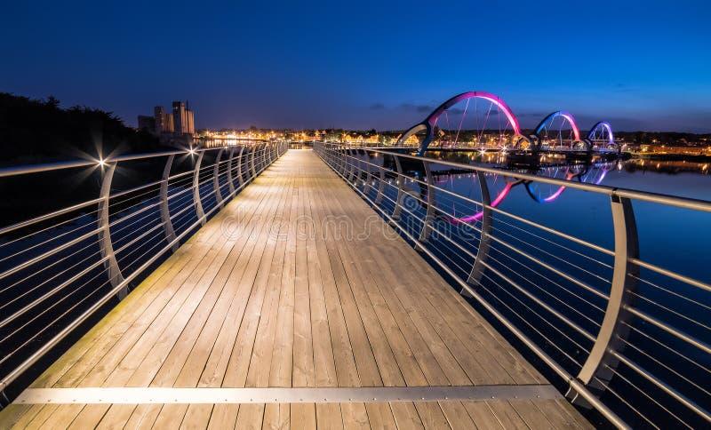 Взгляд ночи для длинного пешеходного моста в Solvesborg на временени стоковое изображение