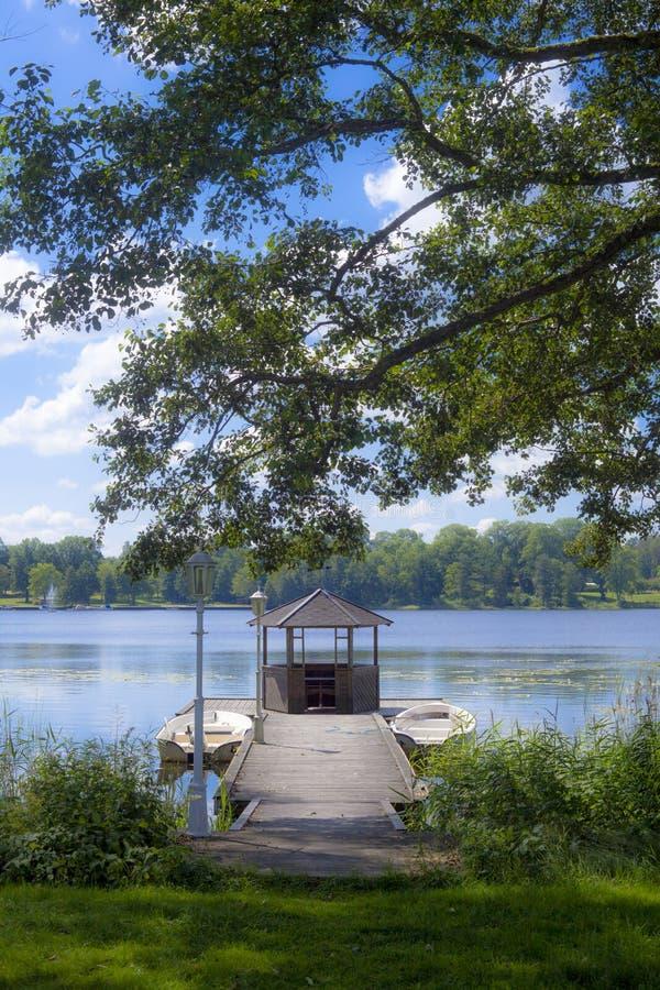 Взгляд озера и вегетации с 2 маленькими лодками причалил на d стоковое фото
