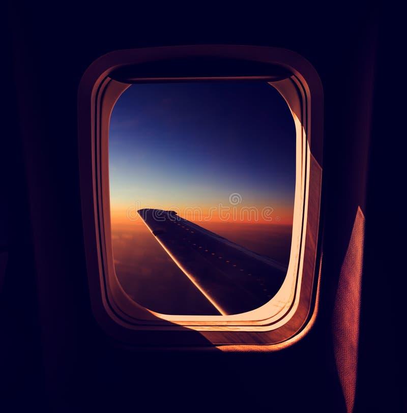 Взгляд от окна самолета на заходе солнца стоковое фото
