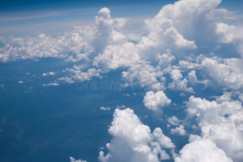 Взгляд от окна самолета показывая голубое небо и белые облака стоковая фотография