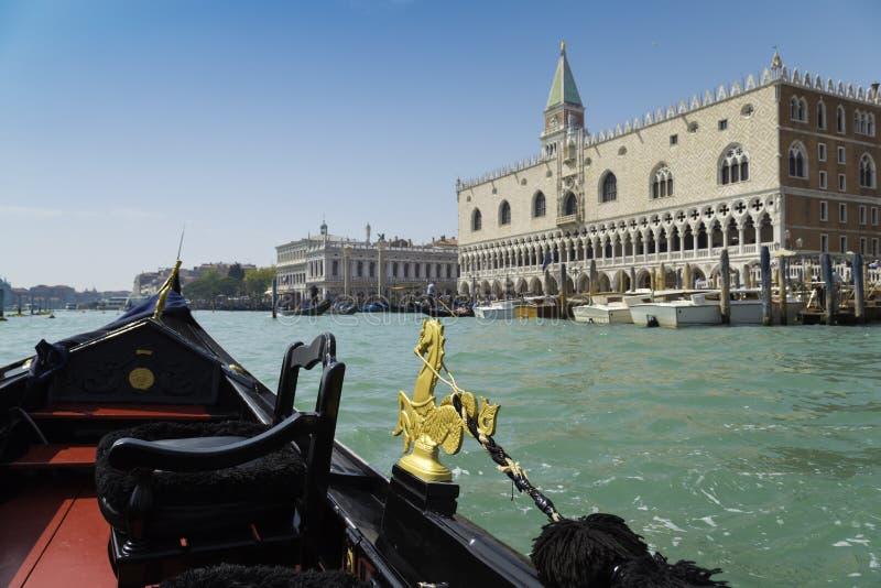 Взгляд от отключения гондолы во время езды через каналы с предпосылкой района Сан Marco в Венеции Италии стоковая фотография