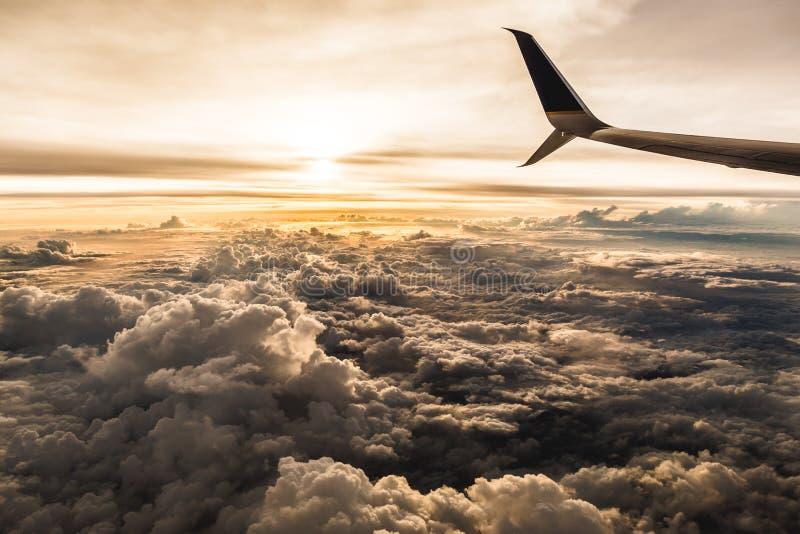 Взгляд пассажира самолета захода солнца над тучными облаками стоковые фотографии rf
