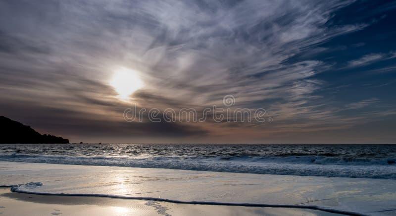 Взгляд пляжа на заходе солнца при облака свертывая внутри стоковые изображения rf