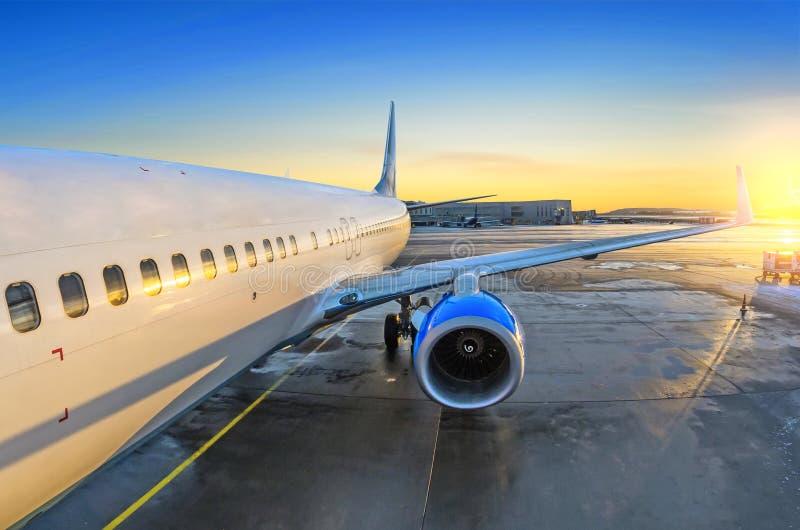 Взгляд самолета пассажира на входе, восходе солнца и автостоянке в двигателе авиапорта стоковые изображения