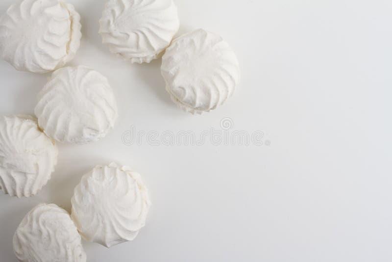 Взгляд сверху латышских marshmallovs - zefiri на белой предпосылке с космосом экземпляра стоковая фотография rf