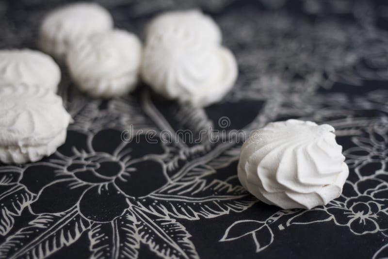 Взгляд сверху латышских marshmallovs - zefiri на белой предпосылке с темной флористической скатертью стоковые изображения rf
