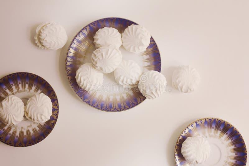 Взгляд сверху латышских marshmallovs - zefiri на плитах фарфора на белой предпосылке, винтажном фильтре стоковое фото rf
