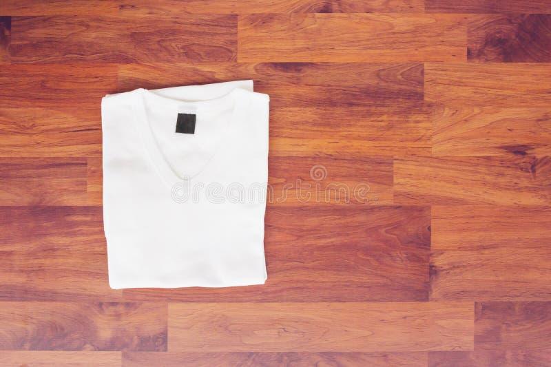 Download Взгляд сверху белой футболки на деревянной предпосылке таблицы Стоковое Фото - изображение насчитывающей ткань, уговариваний: 81803980